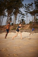 Boys playing soccer on sandy beach