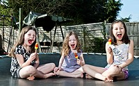 Girls eating popsicles on trampoline