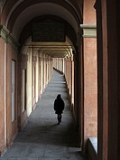 Woman walking under arcade, Bologna, Italy