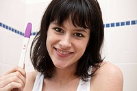 This picture shows a young caucasian woman with brown hair smiling as she watches a pregnancy test