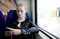 Young, blonde woman, traveling by train from Rotterdam to Nieuwerkerk.
