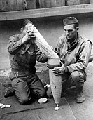 Two U.S. soldiers filling up a shell with medical supplies. The shell will be fired towards isolated Allied units on the border between Belgium and Ge...
