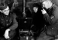 German soldiers listening to music from a gramophone in an encampment on the Russian front near Leningrad, present Saint Petersburg. Leningrad, Decemb...