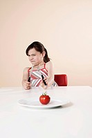 Girl holding a knife and a fork looking disgustedly at a tomato