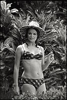 A girl in swimsuit and with a straw hat on her head is a model ofmodern Mexican beauty. She is photographed in a garden vegetation.Mexico, October 196...