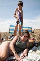 family picture of boy about to squirt his mother with a water pistol while she reads a newspaper on a beach