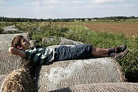 family picture of boy lying down on straw bales in countryside
