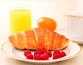 Breakfast. A cup of coffee, croissant, orange juice and berries