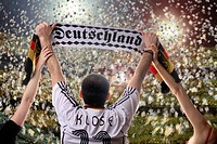 Football fan holding up a German supporters scarf, seen from behind, with confetti in a football stadium