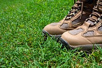 Worn hiking boots standing in green grass.