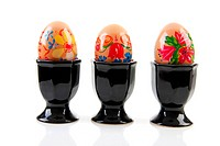 Three chicken eggs decorated by children in black holder over white background