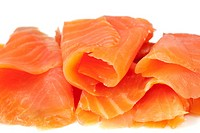 Smoked salmon, sliced and rolled, with white background.