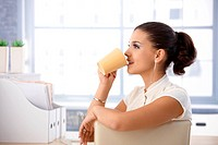 Pretty female casual office worker drinking tea in bright office.