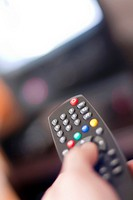 Closeup on a hand changing channels on TV set with a infrared remote