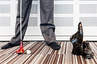 Businessman playing golf in office, low section -