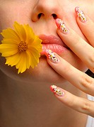Female face close up c flower in a mouth and nail art. Figure of camomiles on nails