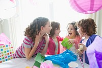 Girls opening gifts at birthday party.