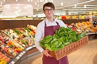 Sales clerk holding box with fresh lettuce