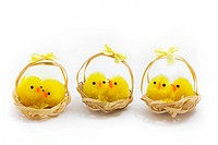 three baskets of easter chicks on a white background