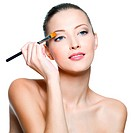 beautiful woman applying eyeshadow with brush _ on white background