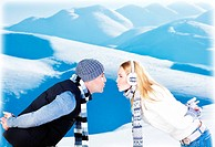 Happy couple kissing, side view face portrait, outdoor at winter snowy mountains, people over natural blue wintertime landscape background, Christmas ...