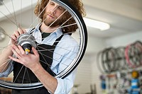 Bike shop owner repairing spokes