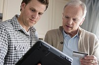 Son helping senior father with internet transaction