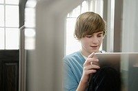 Teenager playing on tablet computer