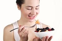 Beautiful young woman eating fruit salad