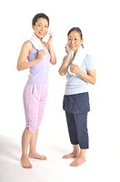 Senior woman and mid adult woman wiping off sweat by towel