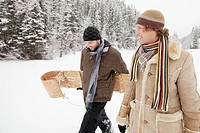 Adult man carrying toboggan