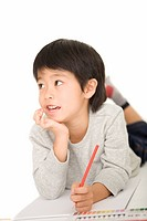 Boy looking away and holding colored pencil