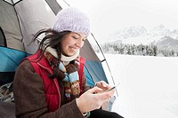 Woman texting from tent in the wintery countryside (thumbnail)