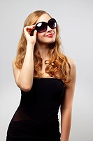 Fashionable lady wearing sunglasses on gray background