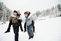 Couples piggy_backing in the snowy outdoors