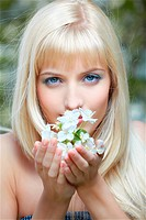 outdoor portrait of beautiful blue_eyed blonde girl posing smelling aroma of flowers