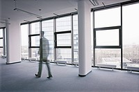 Businessman in motion walking in office hall