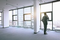 Businessman standing in empty office (thumbnail)