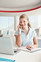 Smiling businesswoman in office talking via cell phone