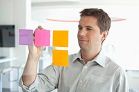 Young businessman writing on post it