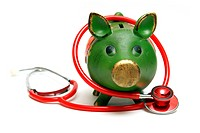 A piggy bank and stethoscope are isolated on white and give representation to an emergency fund.