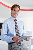 Smiling businessman working on digital tablet