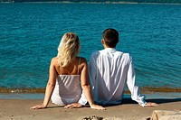 backview of romantic slavonic couple _ blonde girl in peignoir and brown haired man in white shirt taking their time on the beach