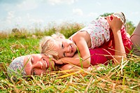 Young woman with cute little girl enjoying a summer day outdoors
