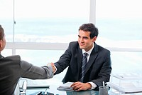 Businessman shaking hands with a client while sitting in an office