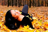 The attractive woman in autumn forest. Lies on yellow leaf