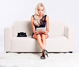 full_length portrait of beautiful young blond woman on couch with tablet pc