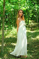 Blond girl in long dress in the summer forest