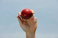 A red cricket ball is held up in the air.