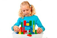 Young blonde girl is playing with colorful wooden blocks over white background